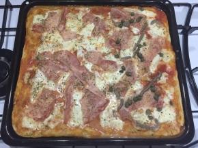Pizza integrale al prosciutto cotto, capperi e acciughe