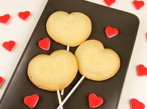 Biscotti a cuore su stecco ripieni di crema pasticcera e crema al cioccolato
